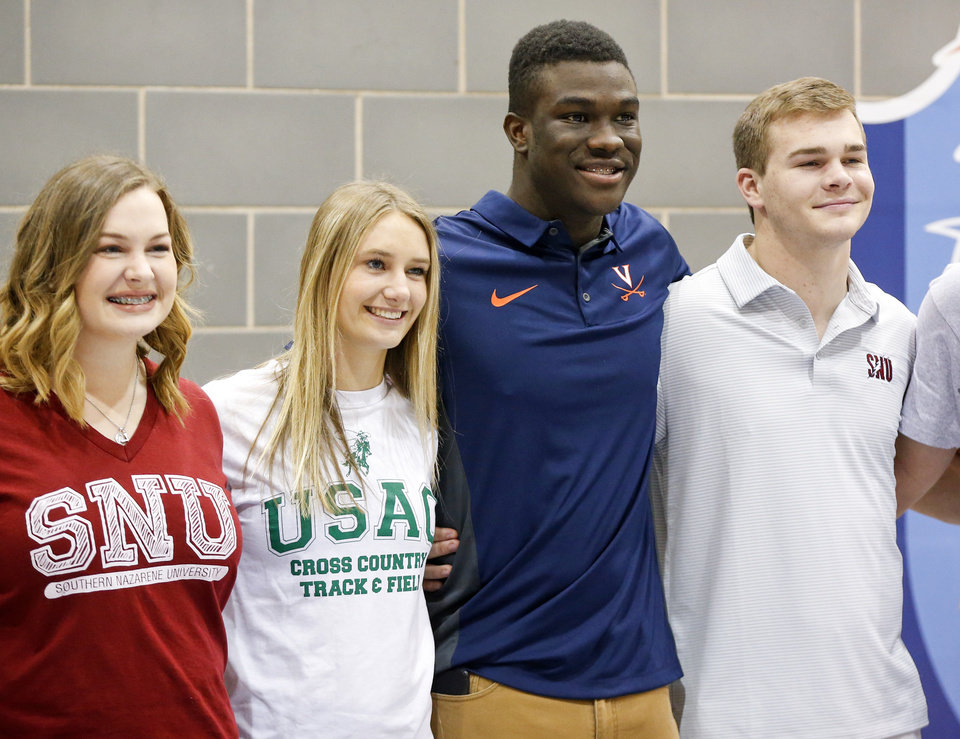 Photo - From left, Emilie Jackson, Mackenzie Holub, Daryl Dike and Tyler Merkley pose for a group photo with other Edmond North athletes during a ceremony for National Signing Day at Edmond North High School in Edmond, Okla., Wednesday, Feb. 7, 2018. Jackson signed to play golf at SNU, Holub to run track at USAO, Dike to play soccer at Virginia and Merkley to play football at SNU. Photo by Nate Billings, The Oklahoman