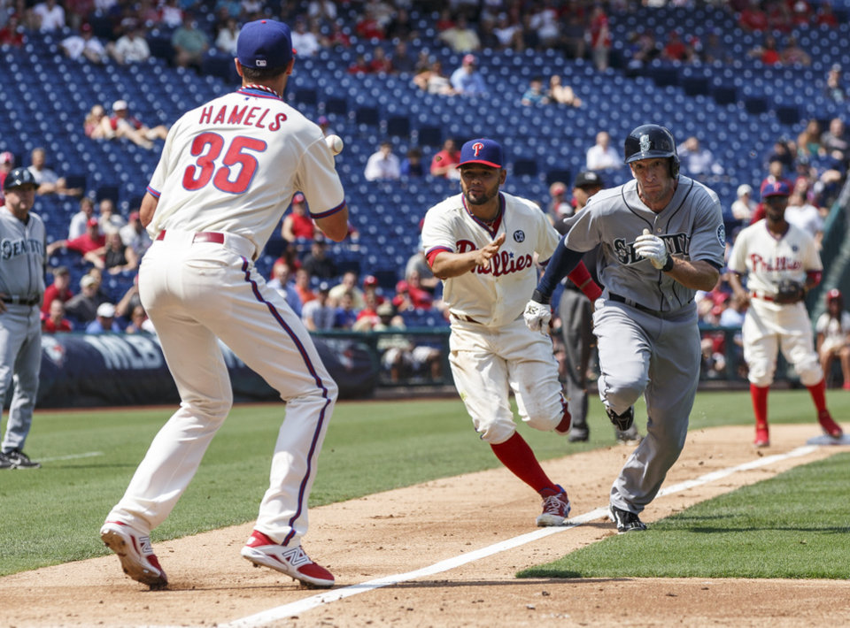 Photo - Philadelphia Phillies third baseman Andres Blanco, center, throws the ball to starting pitcher Cole Hamels, left, as they catch Seattle Mariners' Chris Denorfia, right, stealing during the fourth inning of a baseball game, Wednesday, Aug. 20, 2014, in Philadelphia. (AP Photo/Chris Szagola)