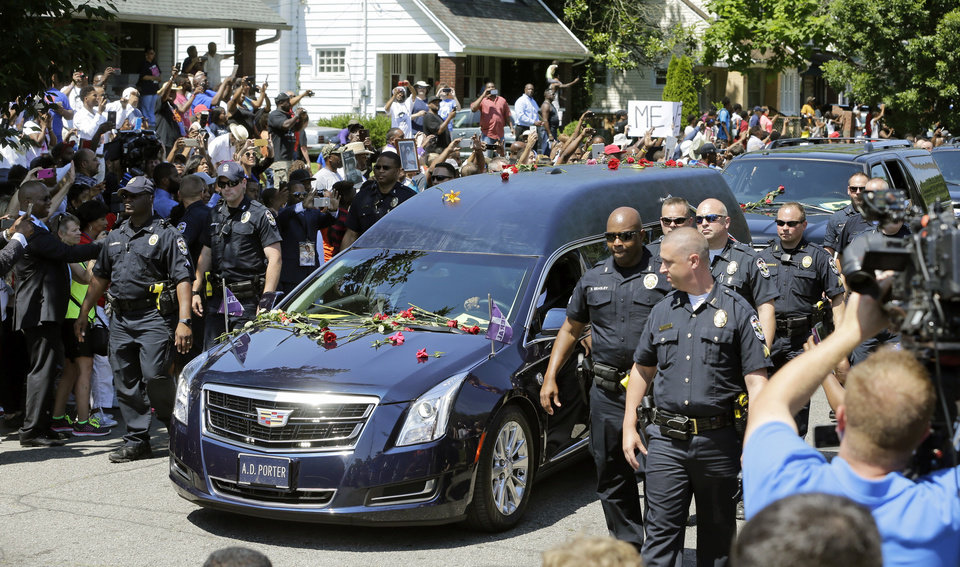 Photo - The hearse carrying the body of Muhammad Ali travels down the street of his boyhood home during his funeral procession Friday, June 10, 2016, in Louisville, Ky. (AP Photo/Mark Humphrey)