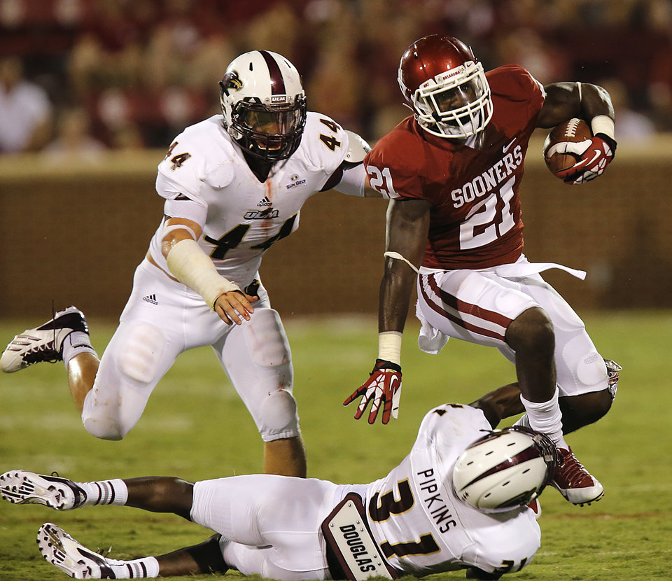 Photo - Oklahoma's Keith Ford (21) runs past Louisiana Monroe's Austin Moss (44) and Lenzy Pipkins (31) during the college football game between the University of Oklahoma Sooners (OU) and the University of Louisiana Monroe Warhawks (ULM) at the Gaylord Family Memorial Stadium on Saturday, Aug. 31, 2013 in Norman, Okla.  Photo by Chris Landsberger, The Oklahoman