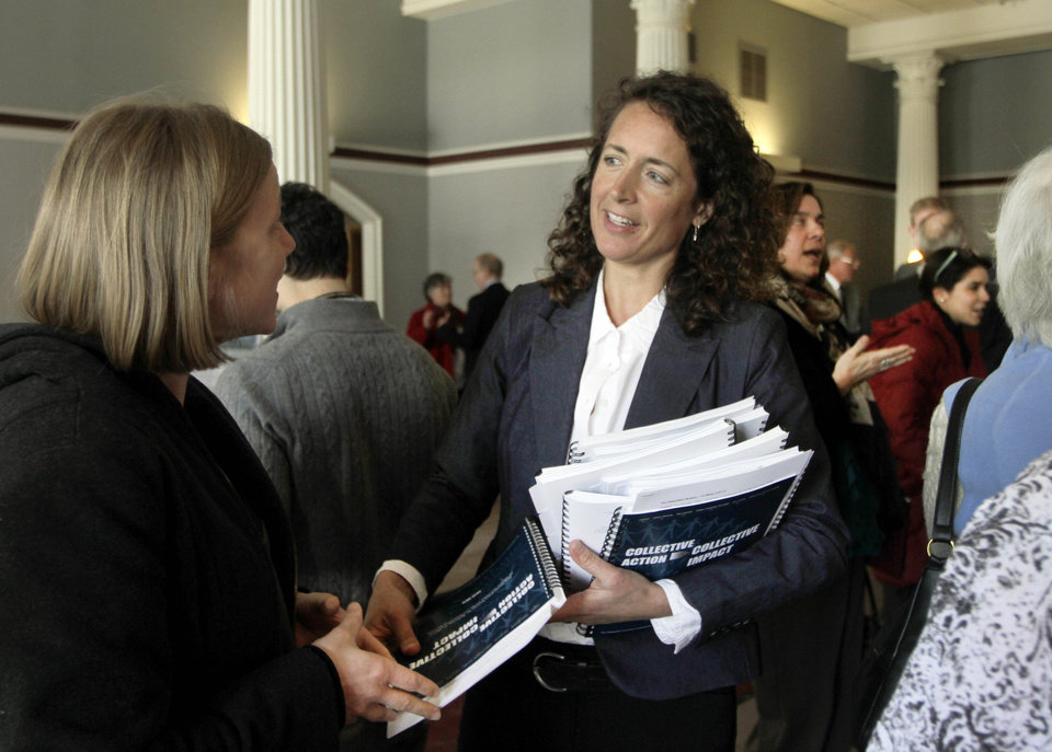 Lisa Mure hands out packets of information as the governor's commission on alcohol and drug abuse prevention releases its five-year plan to reduce substance abuse in New Hampshire., Friday, Feb. 22, 2013 in Concord, N.H. (AP Photo/Jim Cole)