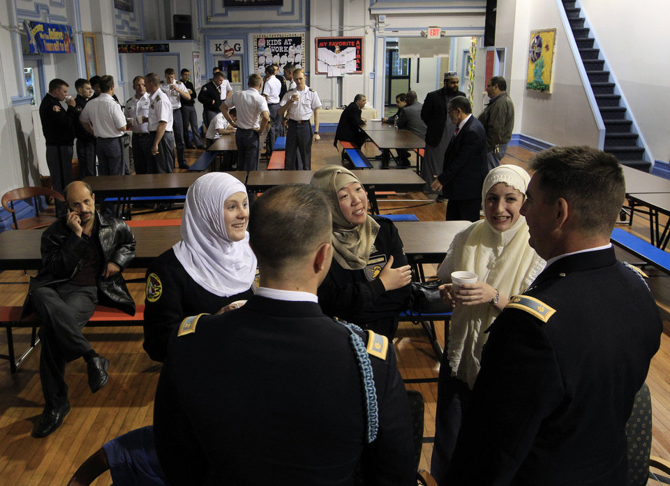 Photo -   Female cadets from the U.S. Military Academy at West Point, N.Y., junior Jordan Reilly, left, and seniors Hana Lee and Megan Kelty, second right, wear Muslim headscarves out of respect during a visit to the Islamic Center of Jersey City as they talk with teachers Maj. Paul Larson, right, and Maj. Andy Gallo Thursday, April 26, 2012, in Jersey City, N.J. The city of 250,000 is one of the most ethnically and religiously diverse places in America, and the cadets are visiting as part of a class at West Point on peacekeeping and reconstruction called