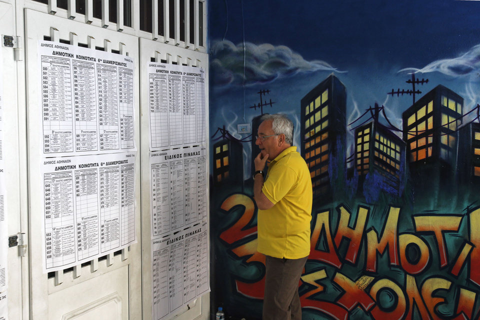 Photo -   A Greek man checks the voting lists at a center voting during the elections in Athens, Sunday, June 17, 2012. Greeks voted Sunday for the second time in six weeks in what was arguably their country's most critical election in 40 years, with the country's treasured place within the European Union's joint currency in the balance. (AP Photo/Petros Karadjias)