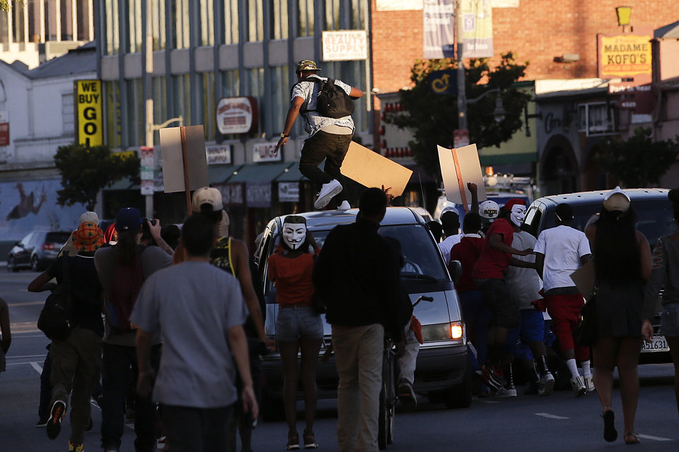 Photo - A protester stomps on a van during a demonstration in reaction to the acquittal of neighborhood watch volunteer George Zimmerman on Monday, July 15, 2013, in Los Angeles. Anger over the acquittal of a U.S. neighborhood watch volunteer who shot dead an unarmed black teenager continued Monday, with civil rights leaders saying mostly peaceful protests will continue this weekend with vigils in dozens of cities. (AP Photo/Jae C. Hong)
