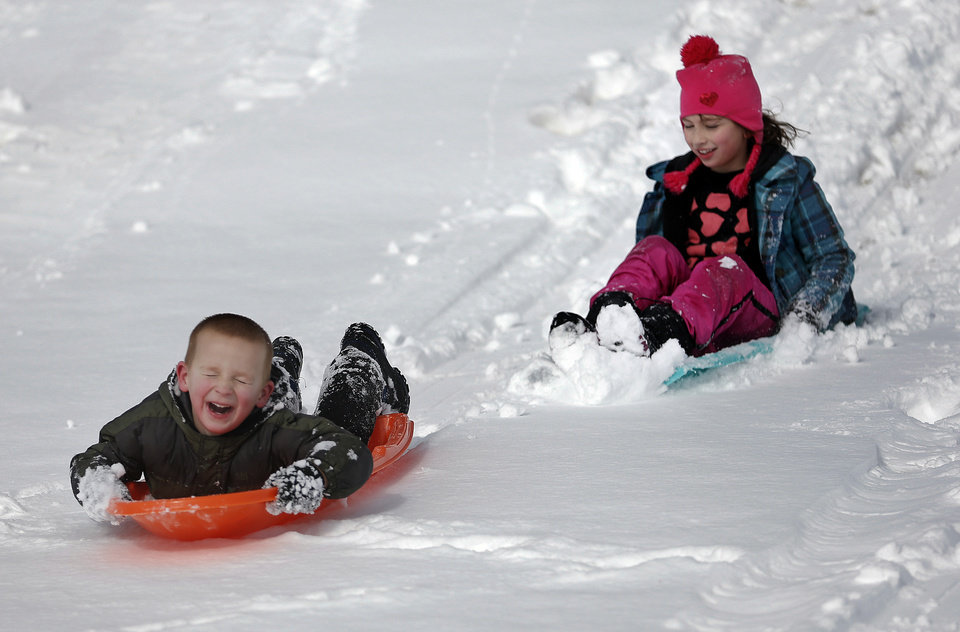Jett Campbell, 4,  and Court Campbell, 4,  sled down a hill in a neighborhood near 164th and Penn in northwest Oklahoma City, Okla.,  Friday, Dec. 6, 2013. Photo by Sarah Phipps, The Oklahoman