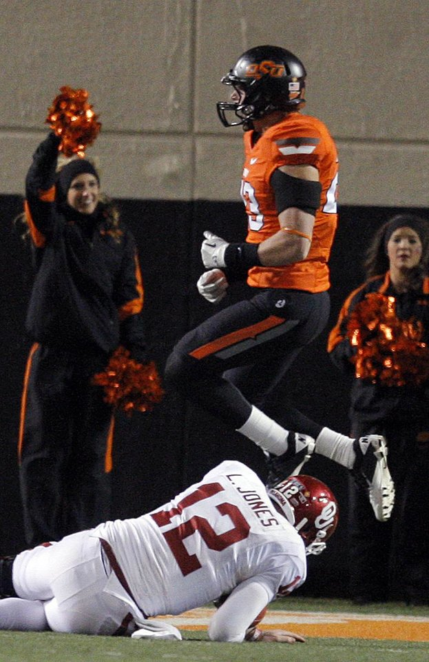 Oklahoma State's Zack Craig (23) celebrates after Oklahoma's Landry Jones (12) is sacked during the Bedlam college football game between the Oklahoma State University Cowboys (OSU) and the University of Oklahoma Sooners (OU) at Boone Pickens Stadium in Stillwater, Okla., Saturday, Dec. 3, 2011. Photo by Sarah Phipps, The Oklahoman