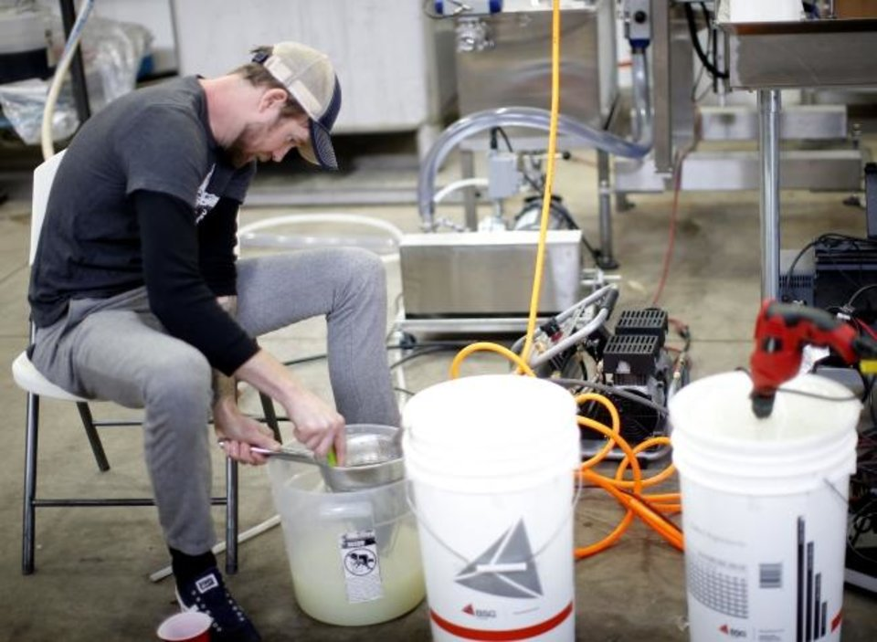 Photo -  Jonathon Stranger mixes hand hand sanitizer at Prairie Wolf Vodka in Guthrie.  [Sarah Phipps/The Oklahoman]