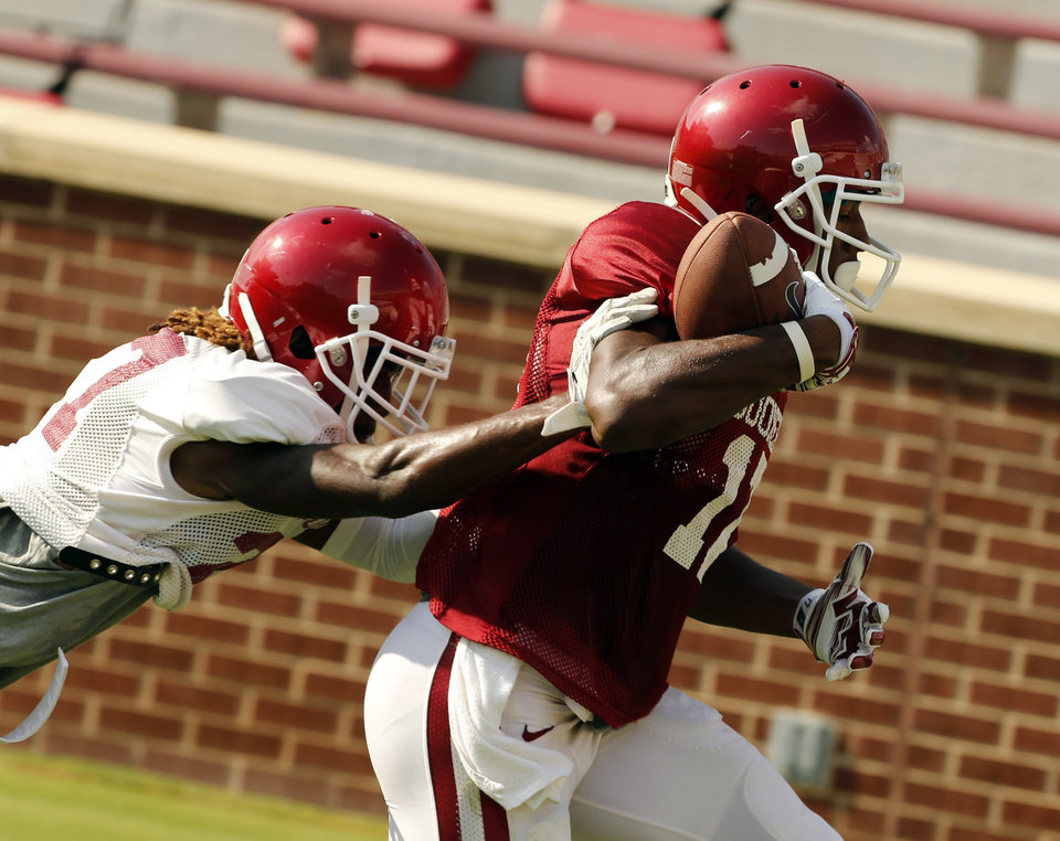 Photo - Oklahoma Sooners's Jordan Smallwood (17) catches a pass in front of Dakota Austin (27) during the University of Oklahoma Sooners (OU) practice and Student Day at Gaylord Family-Oklahoma Memorial Stadium in Norman, Okla., on Thursday, Aug. 21, 2014. Photo by Steve Sisney, The Oklahoman