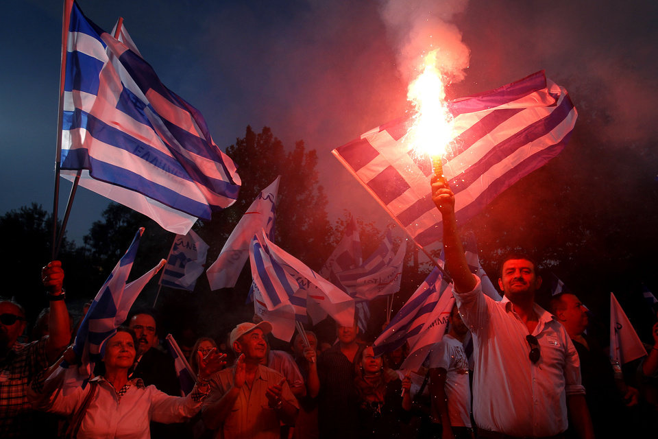 Photo -   Supporters of party 'Independent Greeks' hold flares and wave Greek flags during a pre-election rally of the party, in Athens, on Friday, May 4, 2012, ahead of the Greek general elections scheduled for Sunday, May 6 2012. (AP Photo/Petros Giannakouris)