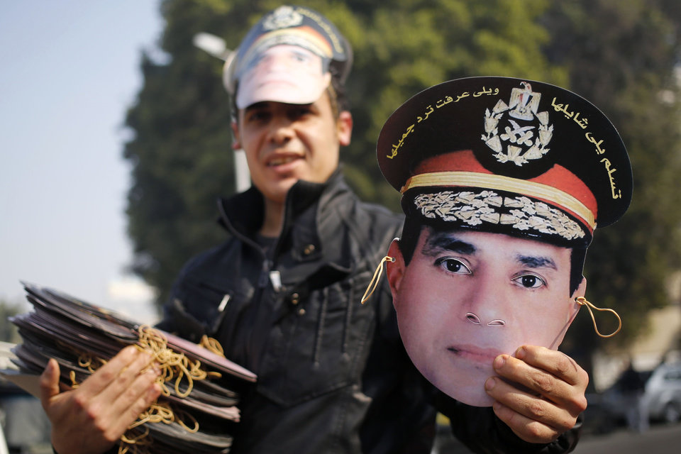 Photo - An Egyptian vendor displays a mask of Egypt's Defense Minister, Gen. Abdel-Fattah el-Sissi, in Tahrir Square, the epicenter of the 2011 uprising, in Cairo, Egypt, Saturday, Jan. 25, 2014. Egyptian riot police have fired tear gas to disperse hundreds of supporters of ousted Islamist President Mohammed Morsi protesting as the country marks the third anniversary of the 2011 uprising, as supporters of the military gathered in rival rallies in other parts of the capital, many of them urging military chief el-Sissi, the man who removed Morsi, to run for president.(AP Photo/Hassan Ammar)