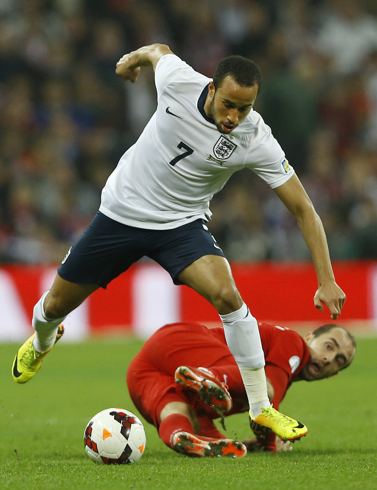 Photo - England's Andros Townsend, leaps over the lunging tackle of Poland's Adrian Mierzejewski during the World Cup Group H qualification soccer match between England and Poland at Wembley stadium in London, Tuesday, Oct. 15, 2013. (AP Photo/Kirsty Wigglesworth)