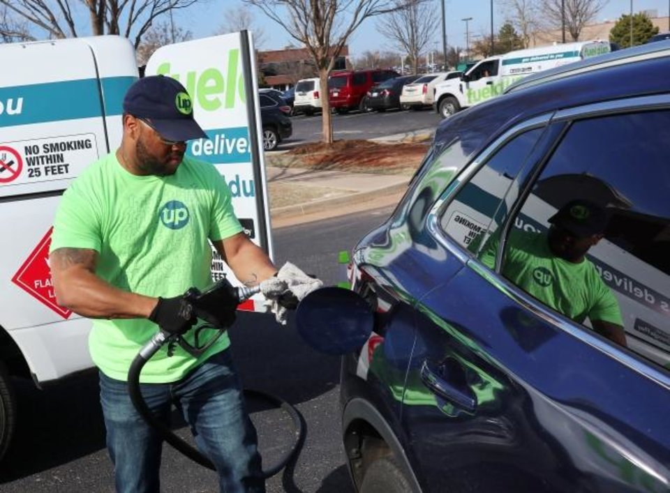 Photo - William Thomas prepares to gas up a car. OKC startup company Fueldup has an app where its clients can request someone fill up their car while they're at work or at home. Tuesday, March 3, 2020.  [Photo by Doug Hoke/The Oklahoman]
