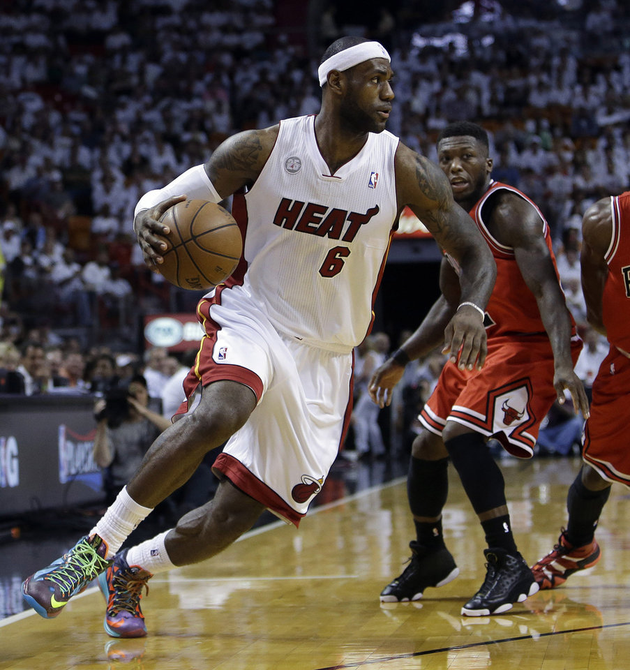 Photo - FILE - In this May 6, 2013 file photo, Miami Heat's LeBron James (6) drives to the basket past Chicago Bulls' Nate Robinson, center, and Jimmy Butler (21) during the first half of Game 1 of the Eastern Conference semifinals, in Miami. NBA legend Michael Jordan believes he could beat James in a one-on-one basketball game when he was in his prime. (AP Photo/Lynne Sladky, File)