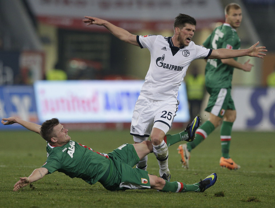 Photo - Schalke's Klaas-Jan Huntelaar of the Netherlands, right, and Augsburg's Daniel Baier challenge for the ball during the German first division Bundesliga soccer match between FC Augsburg and FC Schalke 04, in Augsburg, southern Germany, Friday, March 14, 2014. (AP Photo/Matthias Schrader)