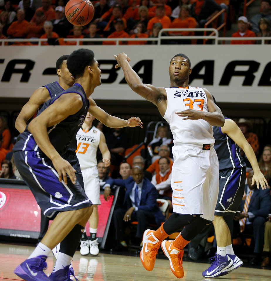 Photo - Oklahoma State's Marcus Smart (33) passes the ball beside TCU's Karviar Shepherd (1) during an NCAA college basketball game between Oklahoma State University (OSU) and TCU at Gallagher-Iba Arena in Stillwater, Okla., Wednesday, Jan. 15, 2014. Oklahoma State won 82-50. Photo by Bryan Terry, The Oklahoman