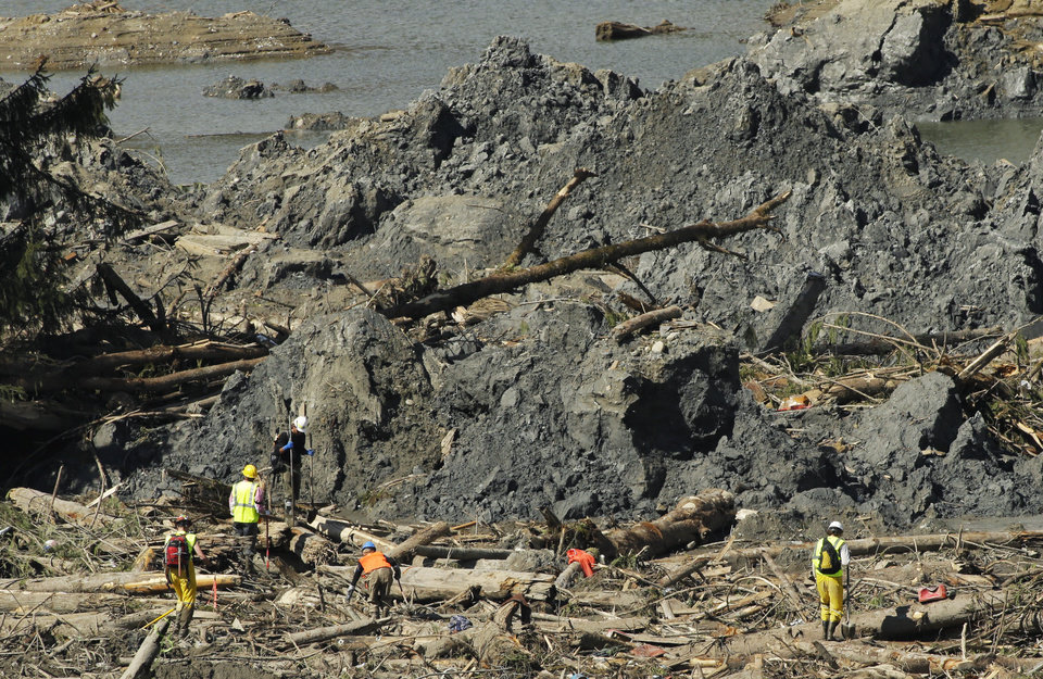 Photo - Workers search an area next to large mounds of dirt Tuesday, April 1, 2014, near Darrington, Wash., in the debris field of the deadly mudslide that hit the community of Oso,Wash. on March 22, 2014. (AP Photo/Ted S. Warren)