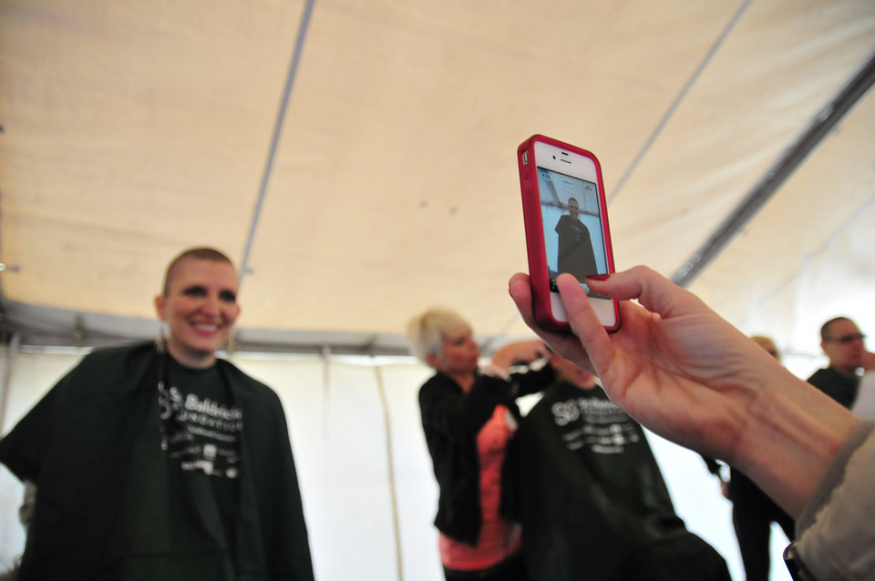 An onlooker takes a photo of the results of Teneil Spaeth getting her head shaved in order to raise money for the St. Baldrick's charity at VZD's Restaurant and Club in Oklahoma City, Okla. Sunday, March 23, 2013.  Photo by Nick Oxford, for The Oklahoman