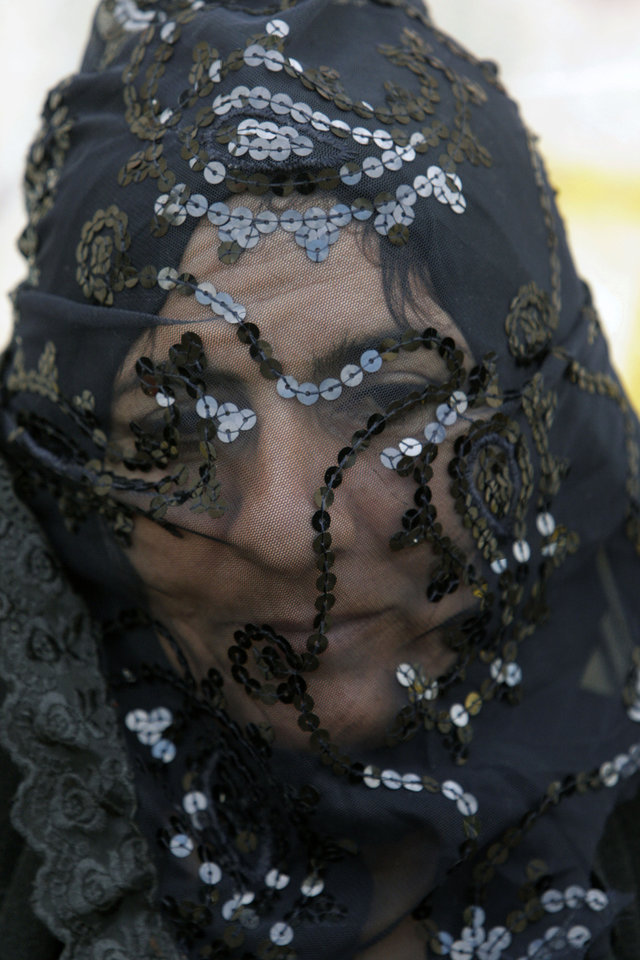 An Iranian woman covers her face symbolically, as she takes part in a mourning ceremony in the city of Khorramabad, southwest of the capital Tehran, Iran, Saturday, Nov. 24, 2012, for Ashoura, marking the death anniversary of Imam Hussein, the grandson of Islam's Prophet Muhammad. Hussein, one of Shiite Islam's most beloved saints, was killed in a 7th century battle at Karbala, Iraq. The ceremony depicts a part of the legend of Imam Hussein's family after being detained by their enemies, and taking them to then capital of Islamic world, Damascus, through forty stations on the road. (AP Photo/Vahid Salemi)