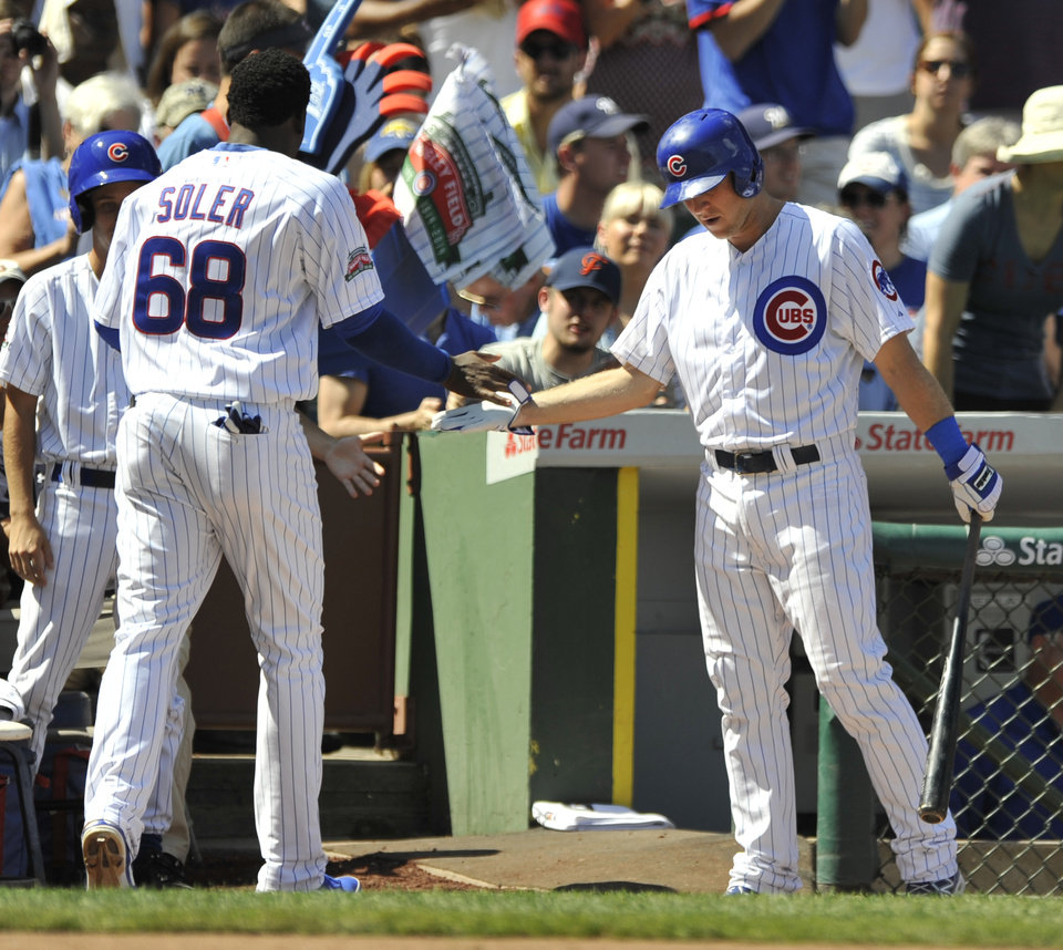 Photo - Chicago Cubs' Jorge Soler (68), celebrates with teammate Chris Valaika right, after scoring on a Welington Castillo single during the second inning of a baseball game against the Milwaukee Brewers in Chicago, Monday, Sept. 1, 2014. (AP Photo/Paul Beaty)