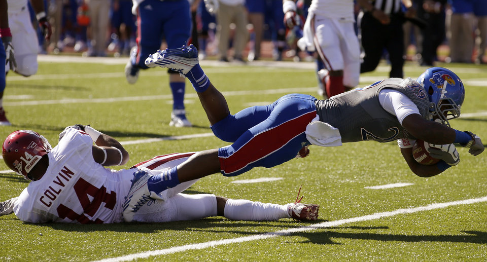 Photo - KU's James Sims (29) leaps past OU's Aaron Colvin (14) during the college football game between the University of Oklahoma Sooners (OU) and the University of Kansas Jayhawks (KU) at Memorial Stadium in Lawrence, Kan., Saturday, Oct. 19, 2013. Photo by Bryan Terry, The Oklahoman