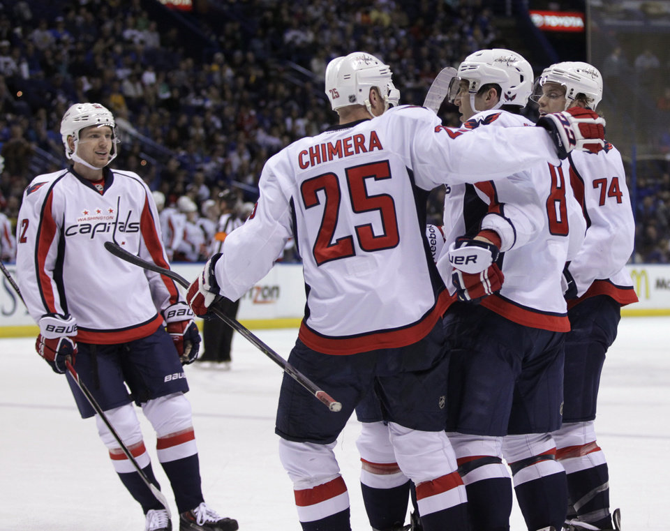 Photo - Washington Capitals' Alex Ovechkin (8) is congratulated by teammates Jason Chimera (25), John Carlson (74) and Mike Green (52) after he scored his 50th goal of the season, during the first period of an NHL hockey game against the St. Louis Blues, Tuesday, April 8, 2014 in St. Louis.(AP Photo/Tom Gannam)