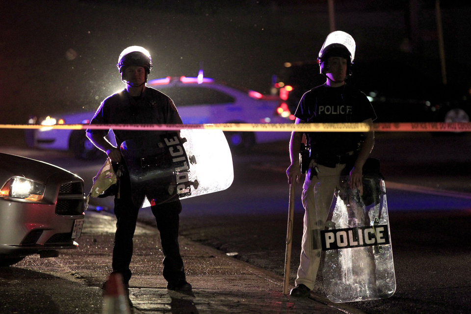 Photo - Police wearing riot gear stand at a post as they wait for a crowd to disperse Monday, Aug. 11, 2014, in Ferguson, Mo. The FBI opened an investigation Monday into the death of 18-year-old Michael Brown, who police said was shot multiple times Saturday after being confronted by an officer in Ferguson. Authorities in Ferguson used tear gas and rubber bullets to try to disperse a large crowd Monday night that had gathered at the site of a burned-out convenience store damaged a night earlier, when many businesses in the area were looted. (AP Photo/Jeff Roberson)
