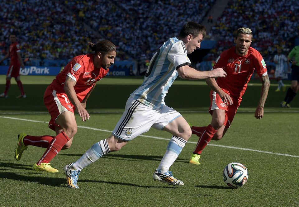 Photo - Argentina's Lionel Messi attacks Switzerland's Ricardo Rodriguez (13) and Valon Behrami during the World Cup round of 16 soccer match between Argentina and Switzerland at the Itaquerao Stadium in Sao Paulo, Brazil, Tuesday, July 1, 2014. (AP Photo/Manu Fernandez)