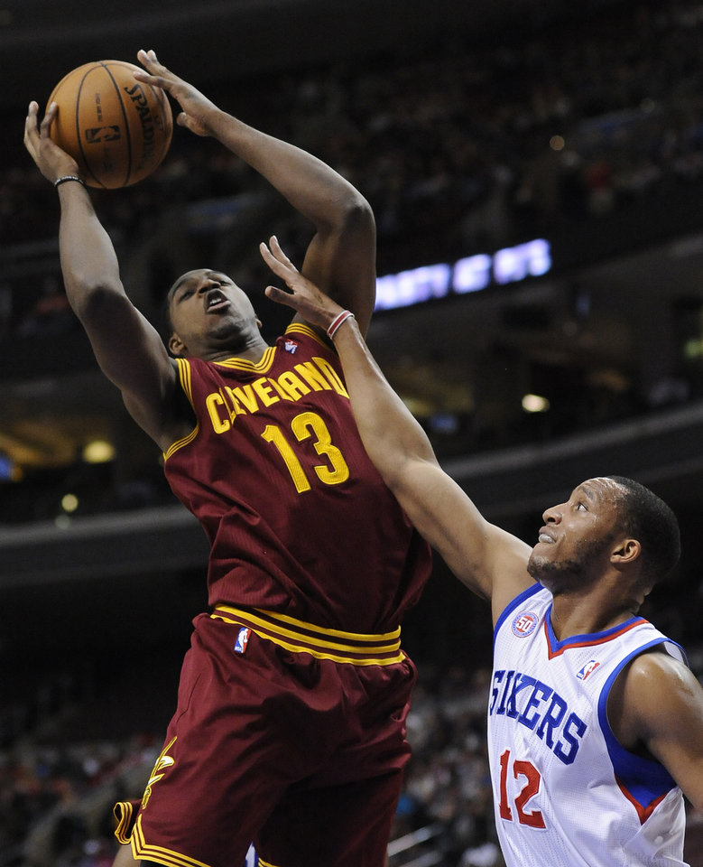 Cleveland Cavaliers' Tristan Thompson (13) shoots over Philadelphia 76ers' Evan Turner (12) during the first half of an NBA basketball game on Sunday, Nov. 18, 2012, in Philadelphia. (AP Photo/Michael Perez)