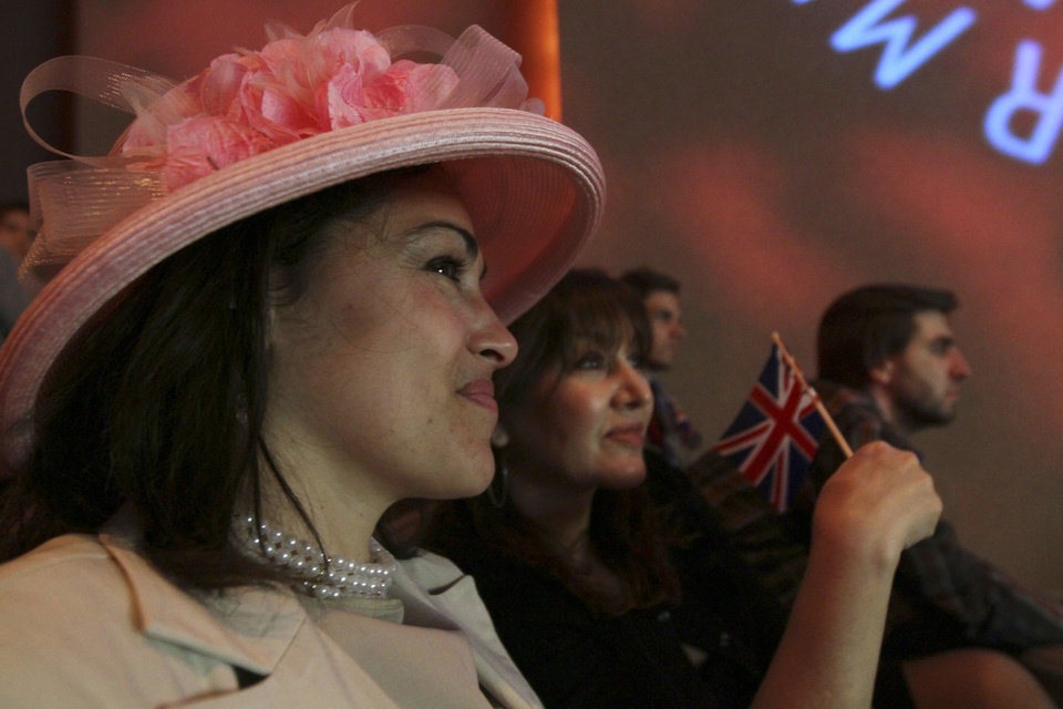 Photo - Wearing a hat for the occasion, Angie Kristic, left, and her friend Jackie Silver, second from left, both from New York, watch coverage of the wedding of Prince William and Kate Middleton as it is broadcast live from London during the Paley Center's royal wedding viewing party Friday April 29, 2011 in New York. (AP Photo/Tina Fineberg) ORG XMIT: NYTF102
