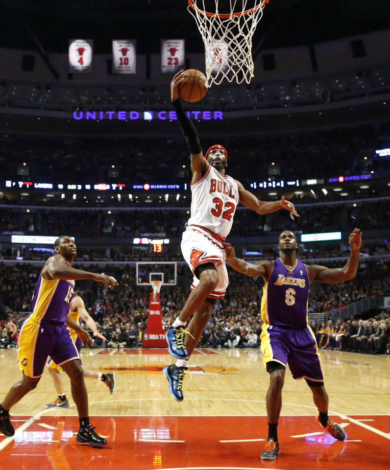 Chicago Bulls guard Richard Hamilton (32) drives to the basket between Los Angeles Lakers' Metta World Peace (15) and Earl Clark (6) during the first half of an NBA basketball game, Monday, Jan. 21, 2013, in Chicago. (AP Photo/Charles Rex Arbogast)