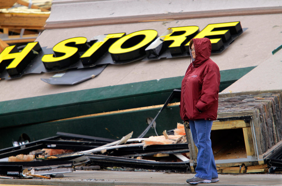 Photo -   Tammy Jenkins take time from cleaning up to survey the damage to a strip mall Friday, March 2, 2012, in Harrisburg, Ill. A pre-dawn twister flattened entire blocks of homes Wednesday as violent storms ravaged the Midwest and South. (AP Photo/Seth Perlman)