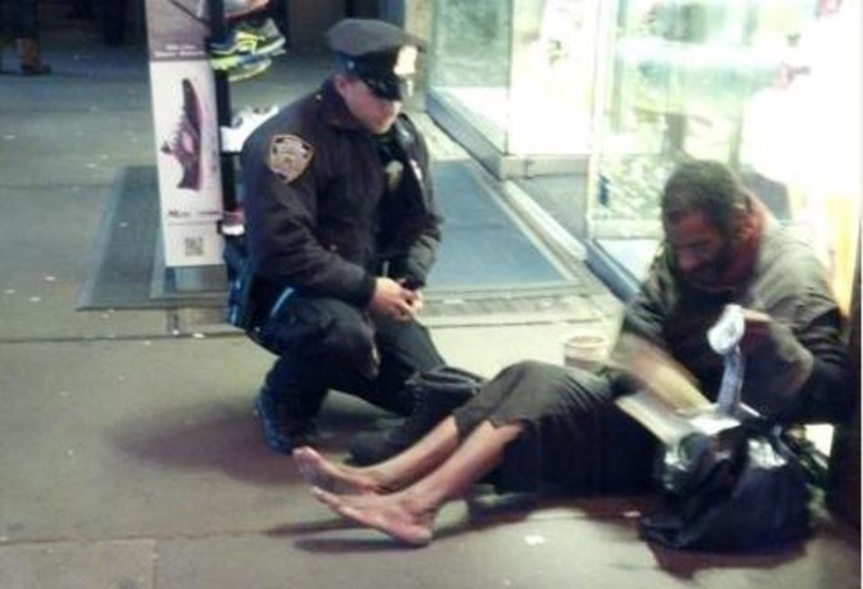 NYPD Officer Larry DePrimo gives a homeless man some socks and boots during a cold October. (Photo courtesy Facebook)