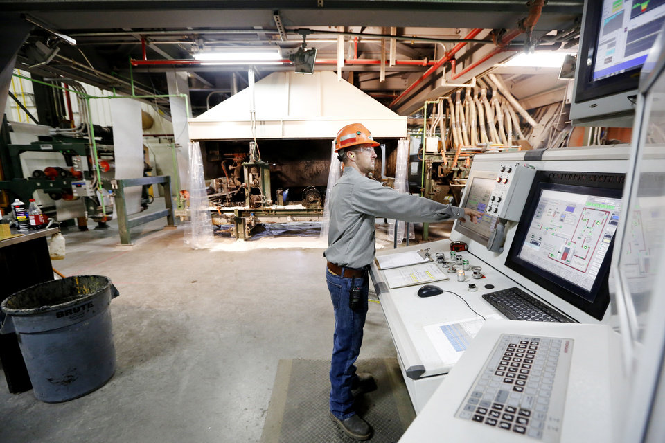 Photo - Malarkey Roofing Products coder operator Cody Blevens monitors a control panel in the production plant in Oklahoma City.  Steve Gooch - The Oklahoman