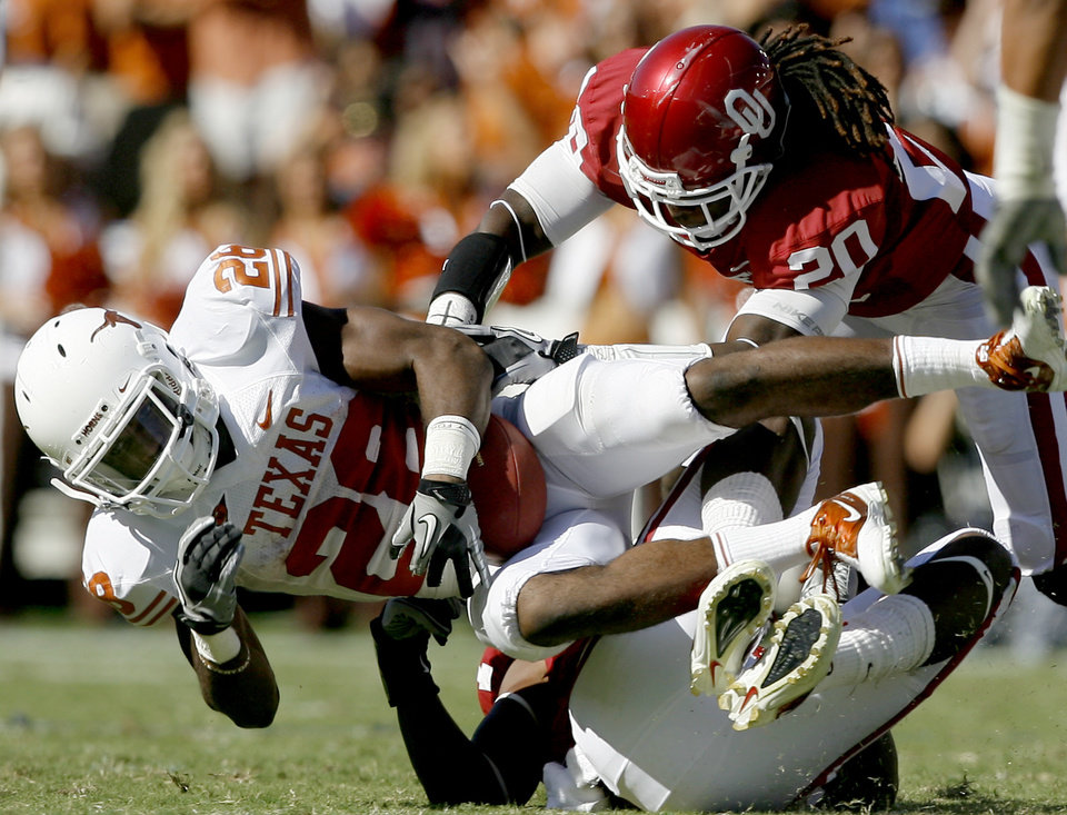 Photo - OU's Quinton Carter helps bring down Fozzy Whittaker of Texas during the first half of the Red River Rivalry college football game between the University of Oklahoma Sooners (OU) and the University of Texas Longhorns (UT) at the Cotton Bowl on Saturday, Oct. 2, 2010, in Dallas, Texas.   Photo by Bryan Terry, The Oklahoman