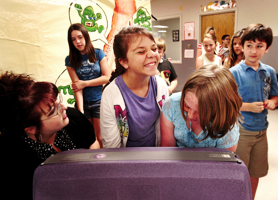 "Photo - Reegan Black, center, reacts when she and fifth-grade classmate Hannah Caves put their hands into a box that has a special light that allows them to see the ""hidden"" germs and dirt on their skin."