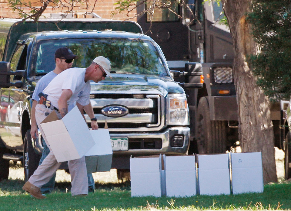 Photo -   An ATF agent arranges boxes for evidence in front of the apartment of James Holmes in Aurora, Colo., Saturday, July 21, 2012. Federal authorities detonated one small explosive and disarmed another inside Holmes' apartment, but several other explosive devices remained, said Aurora police Sgt. Cassidee Carlson. Twelve people were killed and dozens were injured in a shooting attack early Friday at a packed movie theater during a showing of the Batman movie,