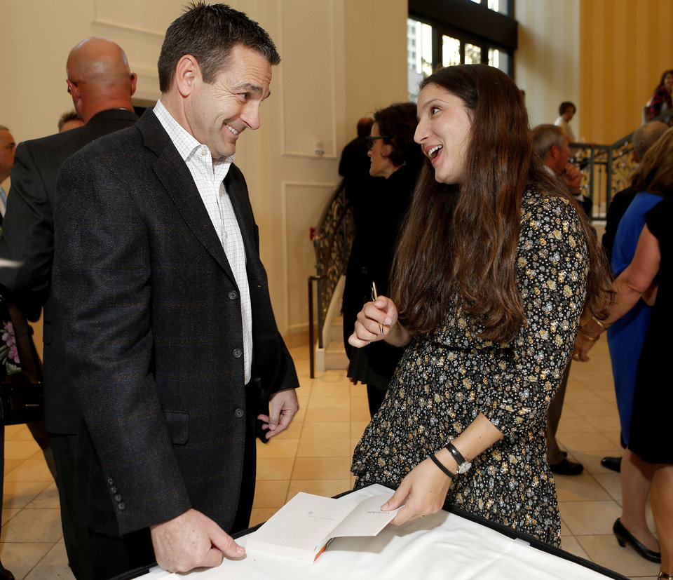 Photo - Author Koren Zailckas speaks with Tim Brooks as she signs a copy of her book for him before during a reception for