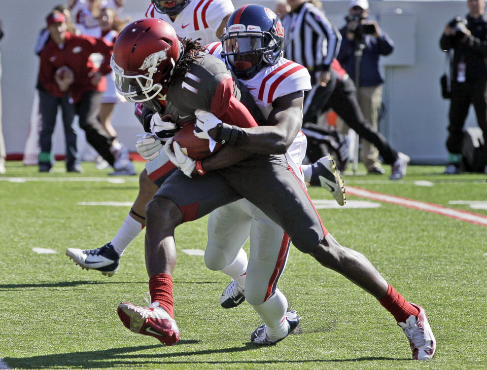 Photo -   Arkansas wide receiver Cobi Hamilton (11) is brought down by Mississippi defensive back Cobi Hamilton during the first quarter of an NCAA college football game in Little Rock, Ark., Saturday, Oct. 27, 2012. (AP Photo/Danny Johnston)