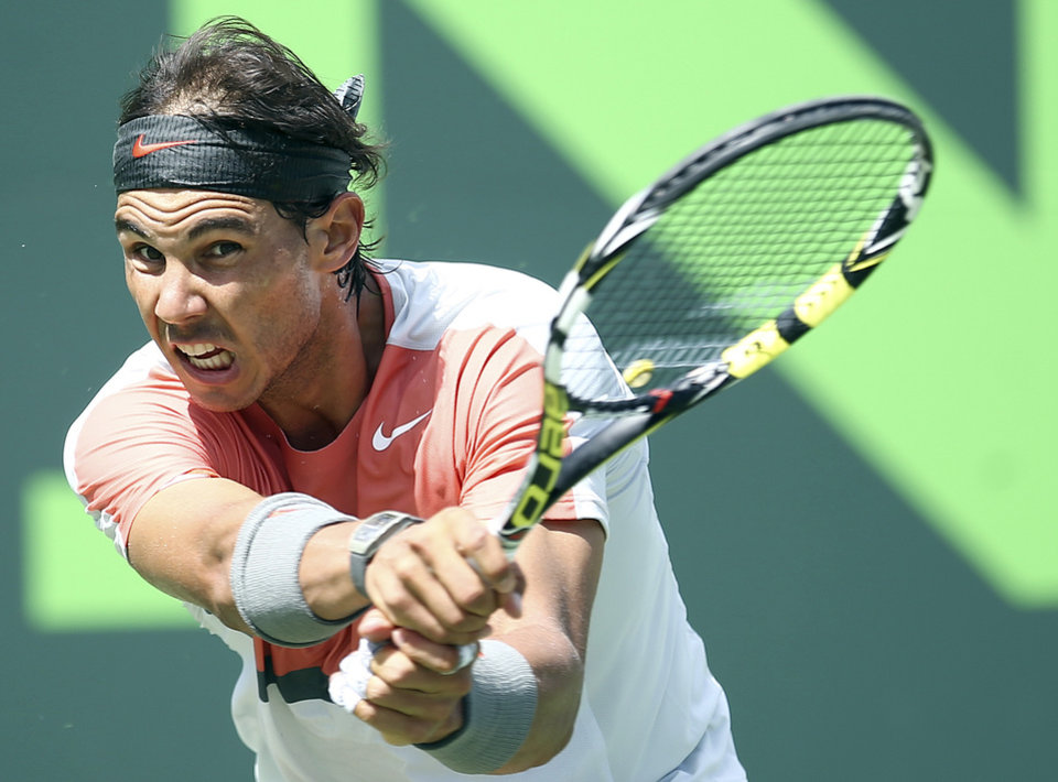 Photo - Rafael Nadal, of Spain, returns a shot from Novak Djokovic, of Serbia, during the men's final match at the Sony Open Tennis tournament on Sunday, March 30, 2014, in Key Biscayne, Fla. (AP Photo/J Pat Carter)