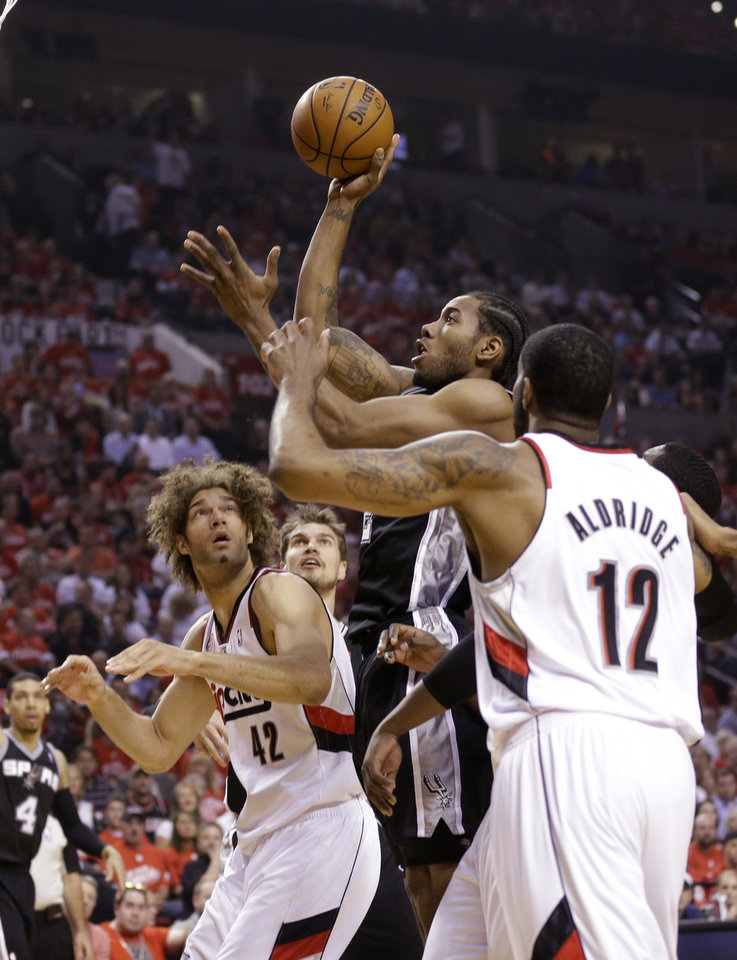 Photo - San Antonio Spurs' Kawhi Leonard, center, shoots as Portland Trail Blazers' Robin Lopez (42) and LaMarcus Aldridge (12) look on in the first quarter during Game 4 of a Western Conference semifinal NBA basketball playoff series Monday, May 12, 2014, in Portland, Ore. (AP Photo/Rick Bowmer)