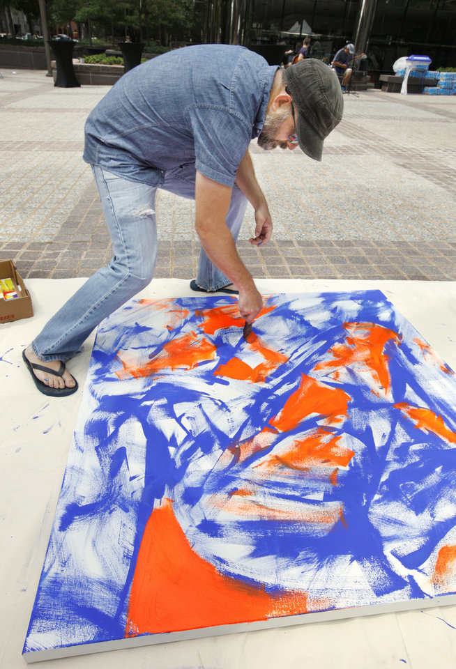 Photo - Artist Ty Kelly, Edmond, works on an acrylic painting at the OK Chefs Relief pop-up at Leadership Square on Monday.  PAUL B. SOUTHERLAND - PAUL B. SOUTHERLAND