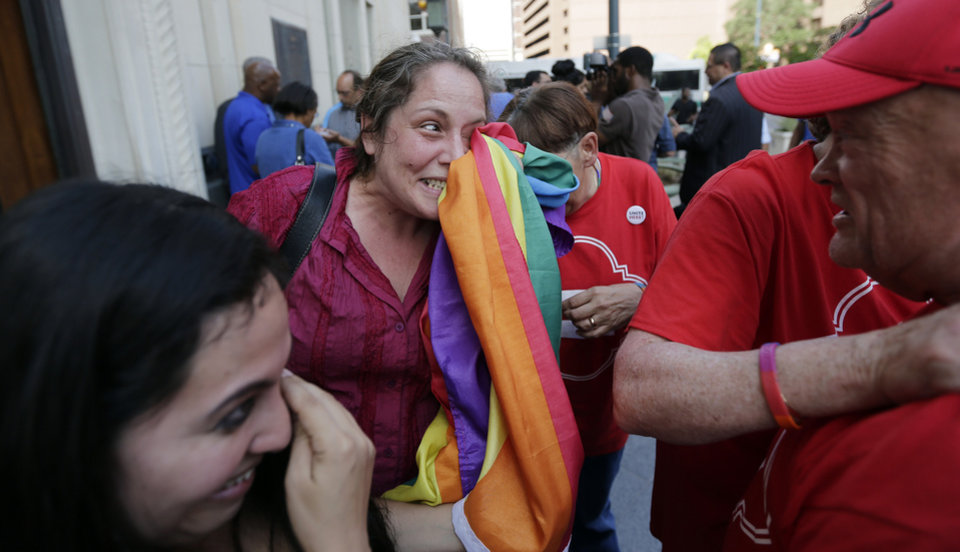 Photo - Julie Pousson, center, wipes away tears as she celebrates after a non-discrimination ordinance was passed by the San Antonio city council, Thursday,  Sept. 5, 2013, in San Antonio. The ordinance in part will prohibit discrimination based on sexual orientation and gender identity.  (AP Photo/Eric Gay)