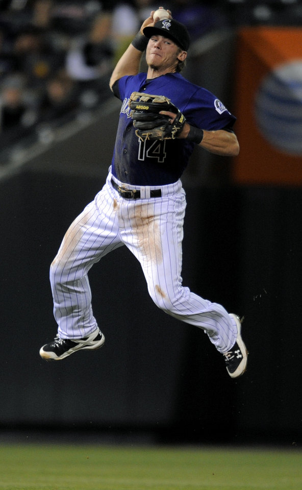 Photo -   Colorado Rockies shortstop Josh Rutledge looks to throws out Justin Upton at first during the fourth inning of a baseball game, Monday, Sept. 24, 2012, in Denver. (AP Photo/Jack Dempsey)
