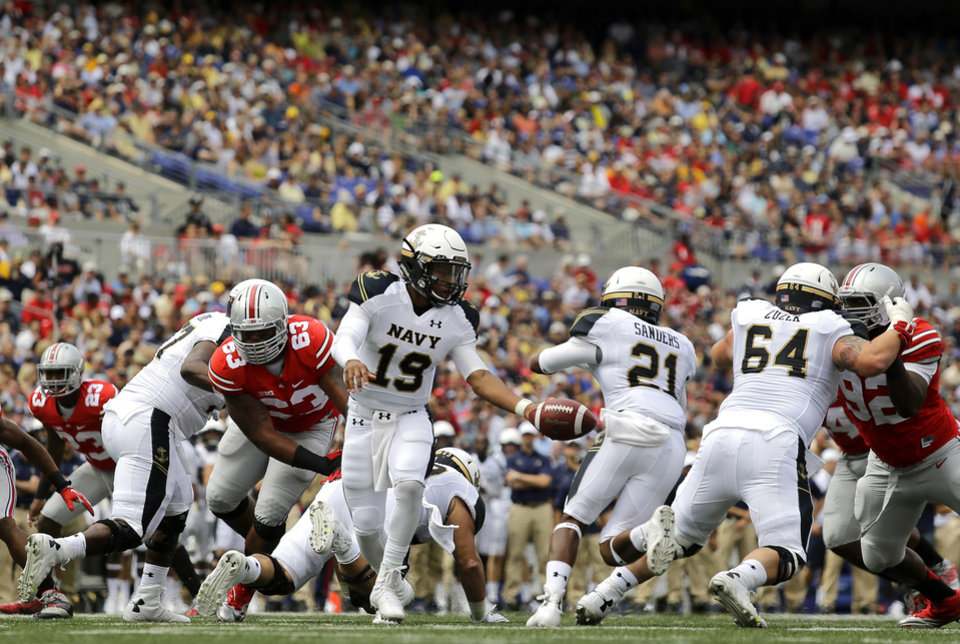 Photo - Navy quarterback Keenan Reynolds (19) hands the ball off to DeBrandon Sanders (21) during the first half of an NCAA college football game against Ohio State in Baltimore, Saturday, Aug. 30, 2014. (AP Photo/Patrick Semansky)