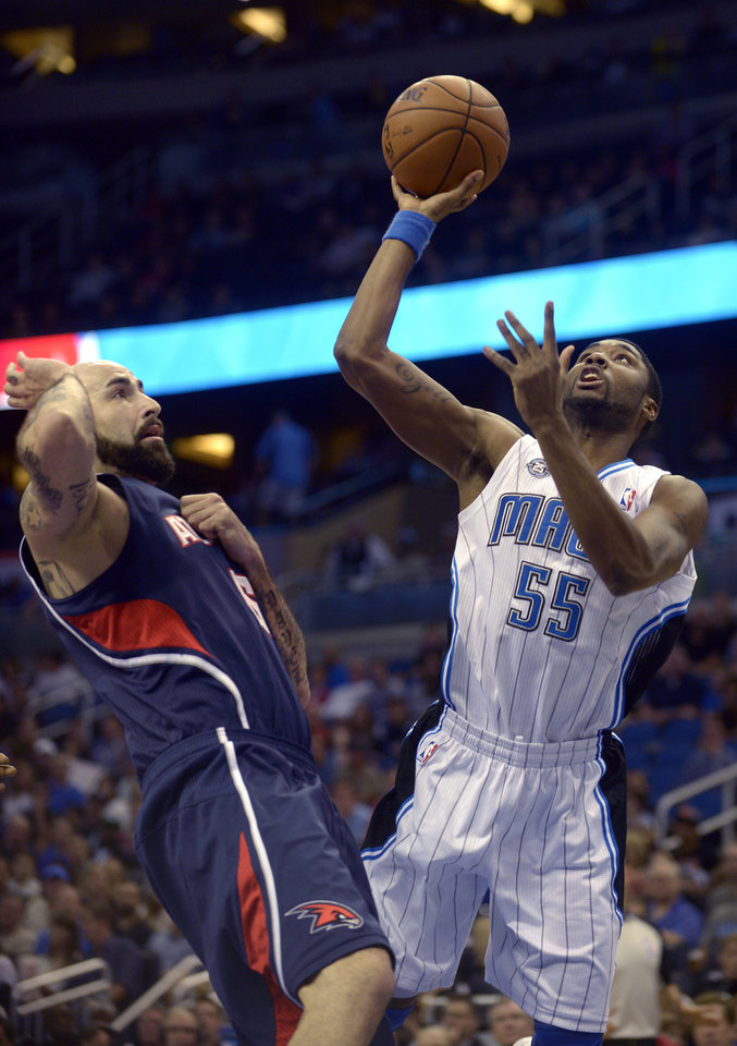 Orlando Magic point guard E'Twaun Moore (55) puts up a shot in front of Atlanta Hawks center Pero Antic (6) during the first half of an NBA basketball game in Orlando, Fla., Sunday, Dec. 29, 2013.(AP Photo/Phelan M. Ebenhack)
