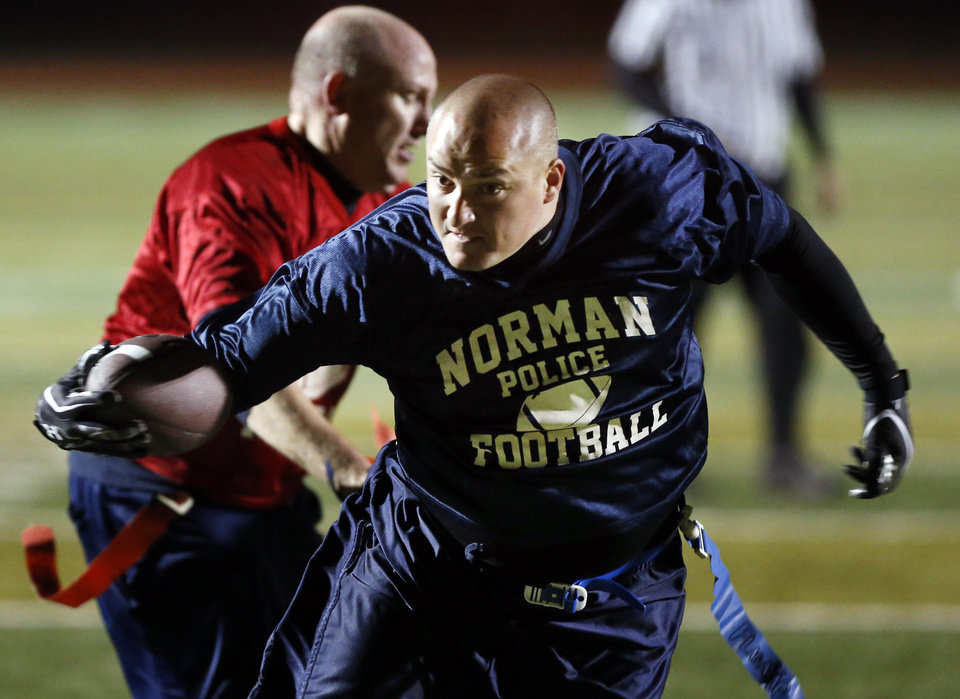Norman policeman Josh Barker runs but was tackled by fireman Jesse Baldwin, behind, during the police and firemen Guns and Hoses charity football game to benefit Compassionate Pointe on Tuesday, Oct. 30, 2012 in Norman, Okla. Photo by Steve Sisney, The Oklahoman