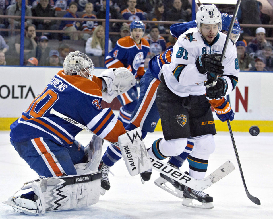 Photo - San Jose Sharks Tyler Kennedy (81) and Edmonton Oilers Justin Schultz battle for the rebound as goalie Ben Scrivens, left, makes the save during the first period of an NHL hockey game in Edmonton, Alberta, on Wednesday, Jan. 29, 2014. (AP Photo/The Canadian Press, Jason Franson)