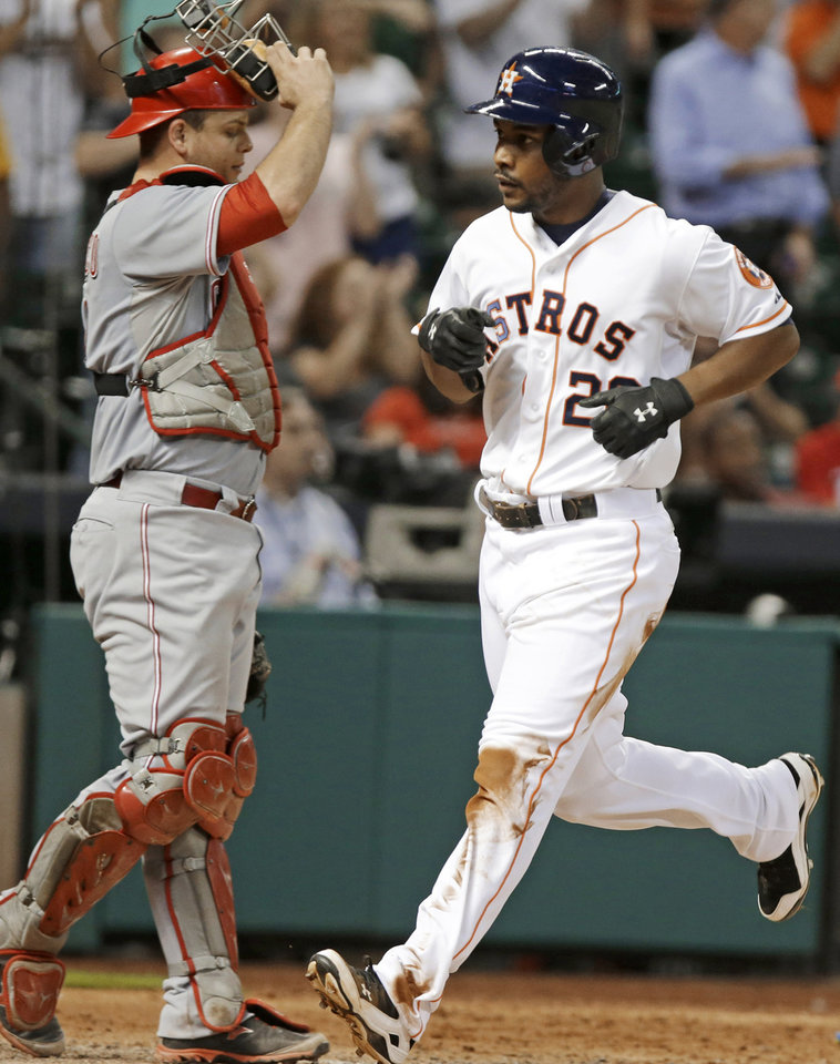 Photo - Houston Astros' L.J. Hoes (28) crosses the plate as Cincinnati Reds catcher Devin Mesoraco heads to the mound in the sixth inning of a baseball game Wednesday, Sept. 18, 2013, in Houston. (AP Photo/Pat Sullivan)