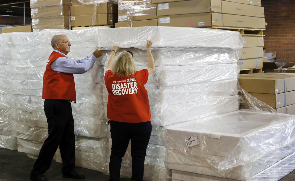 Photo - Ralph Hassel and Elizabeth Disco-Shearer prepare to move mattresses during the recent