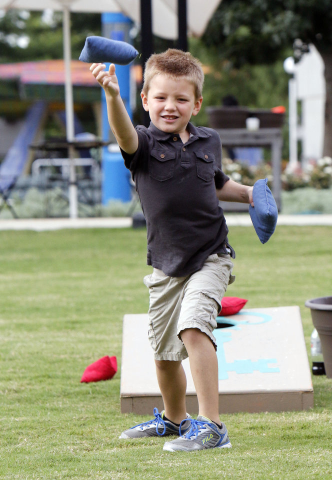Photo -  Grant Sevigny, 6, plays bean bag toss during Games on the Great Lawn at Myriad Gardens. Photo by Paul Hellstern, The Oklahoman   PAUL HELLSTERN -